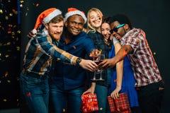 Amis heureux avec le champagne célébrant Noël Images libres de droits