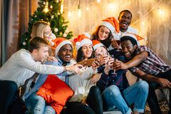 Amis heureux avec le champagne célébrant Noël Image stock