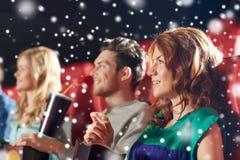 Amis heureux avec le maïs éclaté et boissons dans le cinéma Images stock