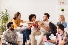 Amis heureux avec le maïs éclaté et la bière à la maison Image stock