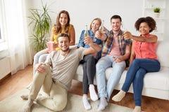 Amis heureux avec le maïs éclaté et la bière à la maison Image libre de droits