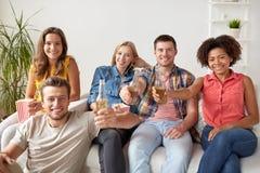 Amis heureux avec le maïs éclaté et la bière à la maison Photo stock