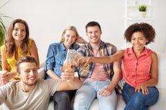 Amis heureux avec le maïs éclaté et la bière à la maison Photos libres de droits