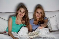 Amis heureux avec le maïs éclaté et la TV de observation à la maison Images libres de droits
