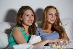 Amis heureux avec le maïs éclaté et la TV de observation à la maison Image libre de droits
