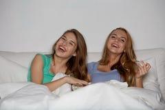 Amis heureux avec le maïs éclaté et la TV de observation à la maison Photographie stock