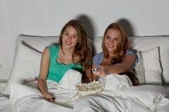 Amis heureux avec le maïs éclaté et la TV de observation à la maison Photo stock