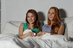 Amis heureux avec le maïs éclaté et la TV de observation à la maison Photos stock
