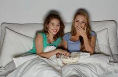 Amis heureux avec le maïs éclaté et la TV de observation à la maison Photographie stock libre de droits