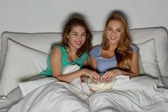 Amis heureux avec le maïs éclaté et la TV de observation à la maison Photo libre de droits