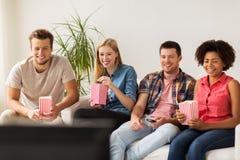 Amis heureux avec le maïs éclaté regardant la TV à la maison Photographie stock