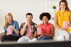 Amis heureux avec le maïs éclaté regardant la TV à la maison Images libres de droits