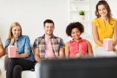 Amis heureux avec le maïs éclaté regardant la TV à la maison Image stock
