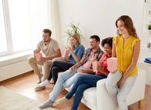 Amis heureux avec le maïs éclaté regardant la TV à la maison Image libre de droits