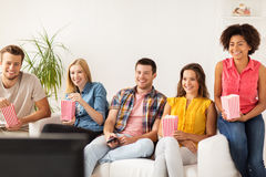 Amis heureux avec le maïs éclaté regardant la TV à la maison Photos stock