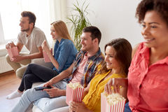 Amis heureux avec le maïs éclaté regardant la TV à la maison Photographie stock libre de droits
