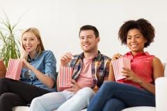 Amis heureux avec le maïs éclaté regardant la TV à la maison Images stock