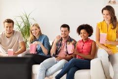 Amis heureux avec le maïs éclaté regardant la TV à la maison Photos libres de droits