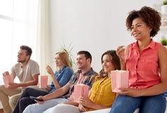 Amis heureux avec le maïs éclaté regardant la TV à la maison Photo libre de droits