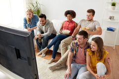 Amis heureux avec le maïs éclaté regardant la TV à la maison Photo stock