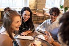 Amis heureux avec le menu au restaurant Images libres de droits