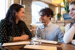Amis heureux avec le menu au restaurant Photos stock