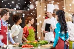 Amis heureux avec le PC de chef et de comprimé dans la cuisine Photos stock