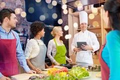 Amis heureux avec le PC de comprimé dans la cuisine Photos stock