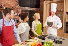 Amis heureux avec le PC de comprimé dans la cuisine Image stock