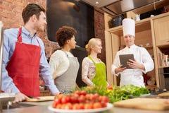 Amis heureux avec le PC de comprimé dans la cuisine Image libre de droits
