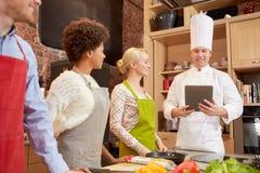 Amis heureux avec le PC de comprimé dans la cuisine Photographie stock libre de droits