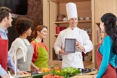 Amis heureux avec le PC de comprimé dans la cuisine Photos libres de droits