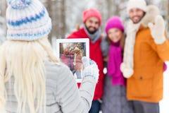 Amis heureux avec le PC de comprimé dans la forêt d'hiver Image libre de droits