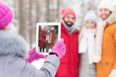 Amis heureux avec le PC de comprimé dans la forêt d'hiver Image stock