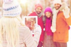 Amis heureux avec le PC de comprimé dans la forêt d'hiver Photo libre de droits