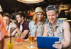 Amis heureux avec le PC de comprimé et boissons à la barre Photos stock