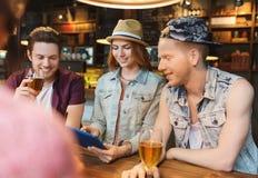 Amis heureux avec le PC de comprimé et boissons à la barre Image libre de droits