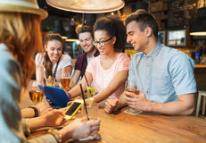 Amis heureux avec le PC de comprimé et boissons à la barre Photographie stock libre de droits