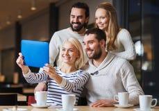 Amis heureux avec le PC de comprimé prenant le selfie au café Images libres de droits