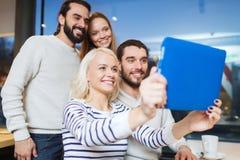 Amis heureux avec le PC de comprimé prenant le selfie au café Photo stock