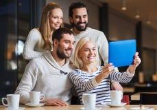 Amis heureux avec le PC de comprimé prenant le selfie au café Photos libres de droits