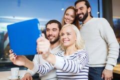Amis heureux avec le PC de comprimé prenant le selfie au café Image libre de droits