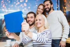 Amis heureux avec le PC de comprimé prenant le selfie au café Photographie stock libre de droits