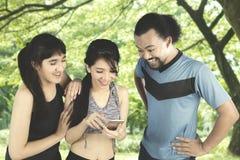 Amis heureux avec le smartphone au parc Photos stock