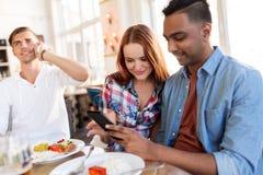 Amis heureux avec le smartphone au restaurant Photo stock