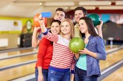 Amis heureux avec le smartphone dans le club de bowling Photos libres de droits