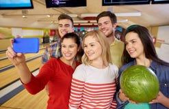 Amis heureux avec le smartphone dans le club de bowling Image stock