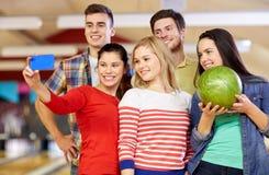 Amis heureux avec le smartphone dans le club de bowling Images libres de droits