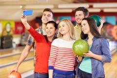 Amis heureux avec le smartphone dans le club de bowling Photographie stock libre de droits
