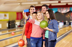 Amis heureux avec le smartphone dans le club de bowling Images stock